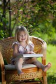 Little girl reading book sitting in wicker chair outdoor in summ — Stock Photo