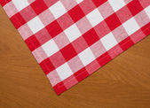 Wooden kitchen table with red gingham tablecloth — Stock Photo