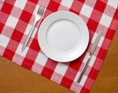 Knife, white plate and fork on wooden table with red checked tab — Stock Photo