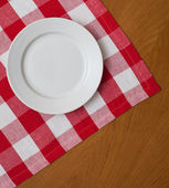 White plate on wooden table with red gingham tablecloth — Stock Photo