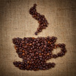 Stock Photo: Coffee cup made from beans on burlap background