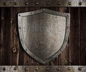 Aged metal shield on wooden medieval gates — Stock Photo