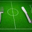 Knife and fork on football field concept — Stock Photo