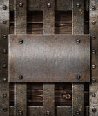 Aged metal plate on wooden medieval background — Stockfoto
