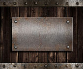 Metal plate on old wooden wall or door — Stock Photo
