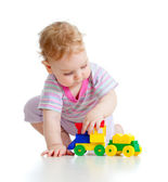 Cute little boy is playing with colorful train isolated on white — Stock Photo