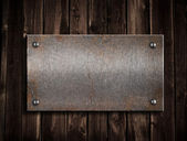 Rusty metal plate on wooden background — Stock Photo