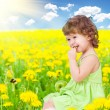 Foto Stock: Baby girl sitting among dandelion with healthy food apple in her