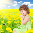 Baby girl sitting among dandelion with healthy food apple in her — Stock Photo