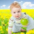 Baby boy among dandelion with healthy food apple in his hand — Stock Photo