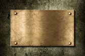 Old golden or bronze plate on wall — Stock Photo