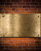 Old golden or bronze plate on brick wall — Stock Photo