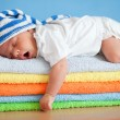 Yawning sleeping baby on colorful towels stack — Stock Photo