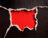 Buraco vermelho com bordas rasgadas em papel preto — Foto Stock