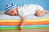 Bebé que duerme en pila coloridas toallas el bostezo — Foto de Stock