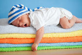 Yawning sleeping baby on colorful towels stack — Foto Stock