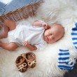 Sleeping newborn baby in wicker basket lying on sheepskin — Stock Photo