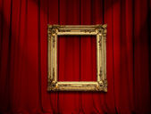 Empty golden painting frame on red curtain wall — Stock Photo