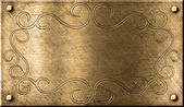 Grunge brass plate with floral pattern — Stock Photo