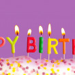 Happy birthday lit candles on purple background — Stock Photo #9536255