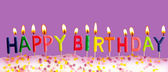 Happy birthday lit candles on purple background — Stock Photo