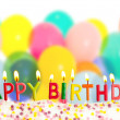 Happy birthday lit candles on colorful balloons background — Stock Photo