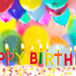Happy birthday lit candles on colorful balloons background — Stock Photo #9749590