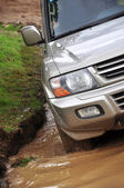 SUV overcomes a pit of mud — Stock Photo