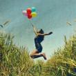 Young woman holding colorful balloons and flying over a meadow. Photo in old color image style. — Stock Photo #10354545