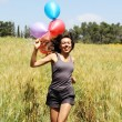 Stock Photo: Young woman with colorful balloons in the field