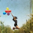 Young woman with colorful balloons in the field — Stock Photo