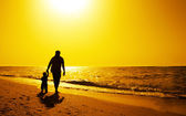 Father and kids silhouettes on the beach at sunset — Stock Photo