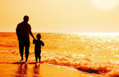 Child with his father at sea on sunset — Stock Photo