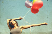 Young woman holding colorful balloons and flying over a meadow. Photo in old color image style. — Stock Photo