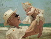 Happy grandpa is holding a little granddaughter. — Stock Photo