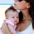 Mother with her baby on the beach — Stock Photo #8761713