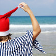 Stock Photo: Christmas at sea. Girl in Santa hat on the beach.