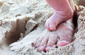 Mom's and baby's feet on the beach — Stock Photo