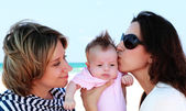 Two beautiful girls with a baby on the beach — Stock Photo
