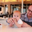 Royalty-Free Stock Photo: Dad with his baby daughter in a cafe ordering breakfast