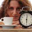 Beautiful girl with cup of coffee and clock — Stock Photo
