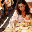 Young mother with her daughter in a cafe eating breakfast — Stock Photo