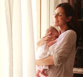 30-year-old beautiful mom is holding her newborn daughter — Stock Photo