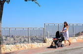 Young mother walking with a stroller on the background of a big — Stock Photo