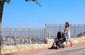 Mladá matka chůzi s kočárku na pozadí velké — Stock fotografie
