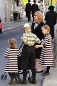 Children and adults dressed in traditional Jewish clothing, cross the road — Stock Photo