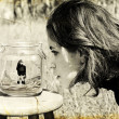 Royalty-Free Stock Photo: Girl looks at herself in the glass jar. Photo in old image style