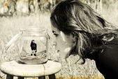 Girl looks at herself in the glass jar. Photo in old image style — Stock Photo