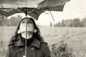 Girl with umbrella in the field. Photo in old color image style. — Stock Photo