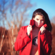 Stock Photo: Brunette womin red coat with underwear outdoor